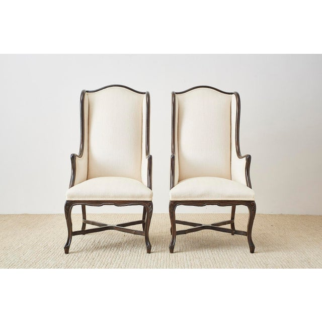 Exceptional pair of hand carved walnut wingback chairs featuring an exposed frame design. Made in the French Louis XV...