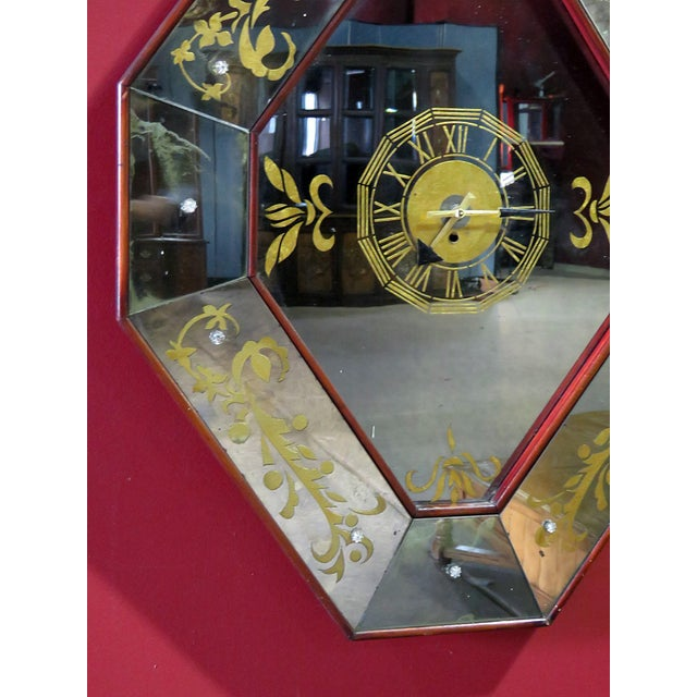 Regency style eglomise mirrored wall clock with wood trim.