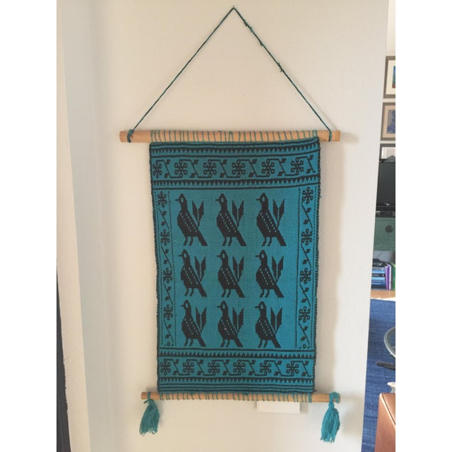 This vintage, loomed wall hanging features a saturated teal and black color palette. Clean wooden dowels accented by teal...