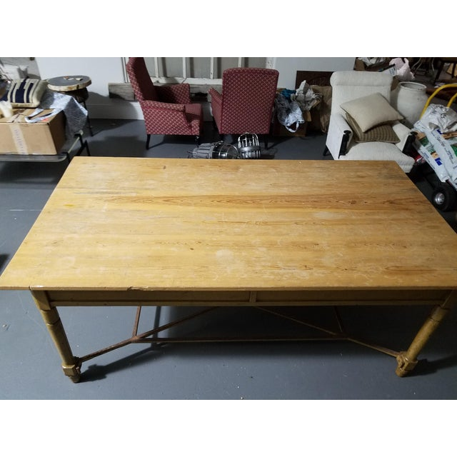 French farm table with painted yellow, natural top and iron stretcher. Circa early 1900s.