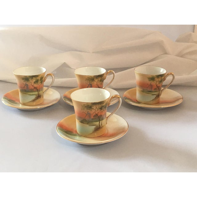 Vintage set of hand painted china cups and saucers with gold trim feature a windmill silhouetted against the vibrant...