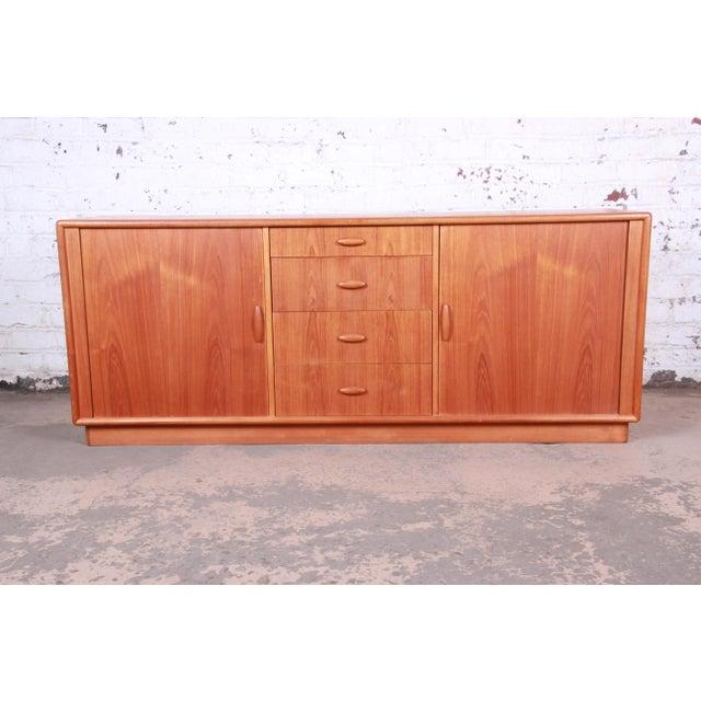 A gorgeous mid-century Danish Modern teak credenza or long dresser by Dyrlund. The credenza features stunning teak wood...
