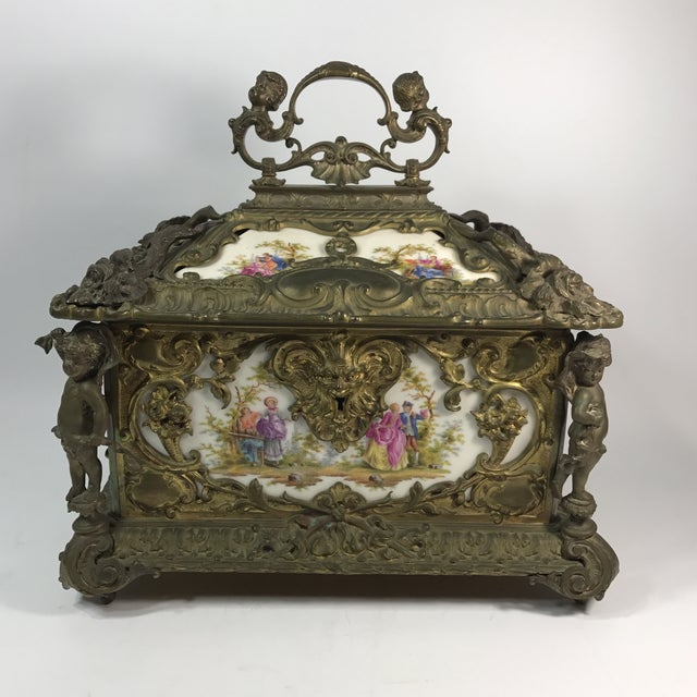 An antique Kpm jewelry box heavily gilded bronze baroque style. Eight hand painted porcelain plaques of courting scenes...