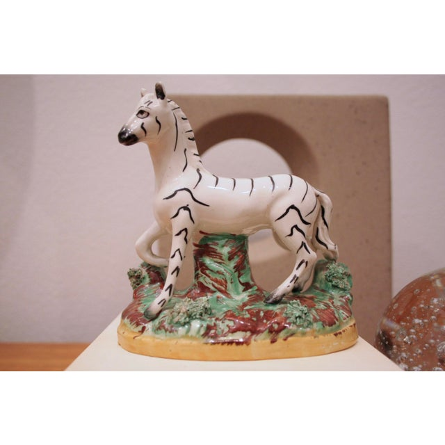 Wonderful small scale glossy glazed zebra figure. Perfect on a stack of books or on a nightstand where larger pieces may...