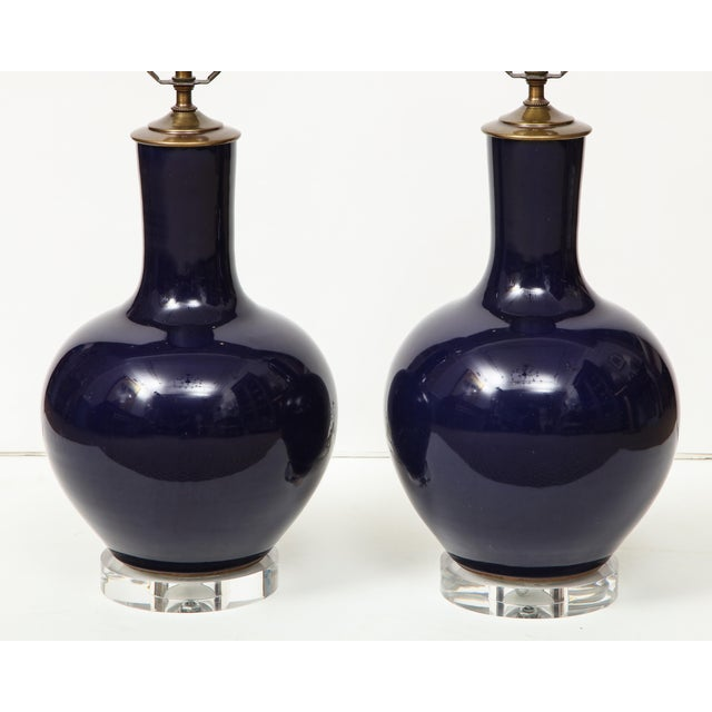 A pair of Chinese ceramic vase lamps in a deep navy blue on Lucite base. These lamps add a nice color to any room while...