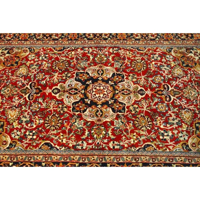 Classic Persian Isfahan rug featuring a center medallion and intricate patterns of palmettes and arabesque designs....