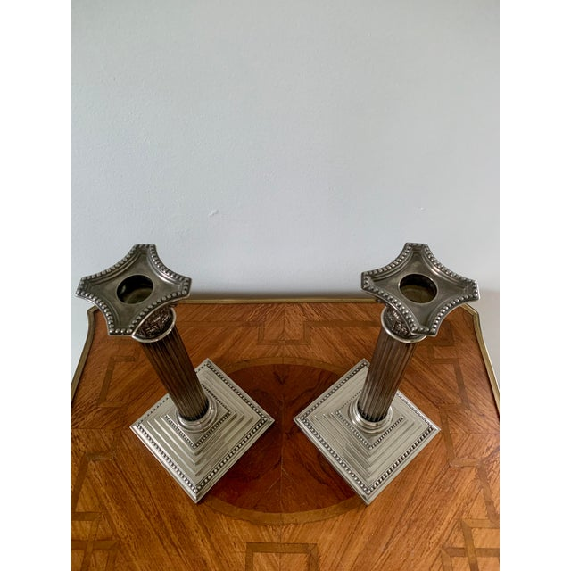 A pair of stately silver-plate corinthian column candlesticks made by Godinger.