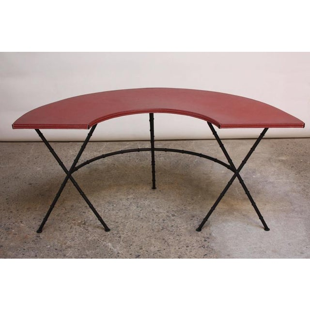 This 1950s demilune table/desk is comprised of a hand-stitched red leather surface (likely a later but vintage addition to...