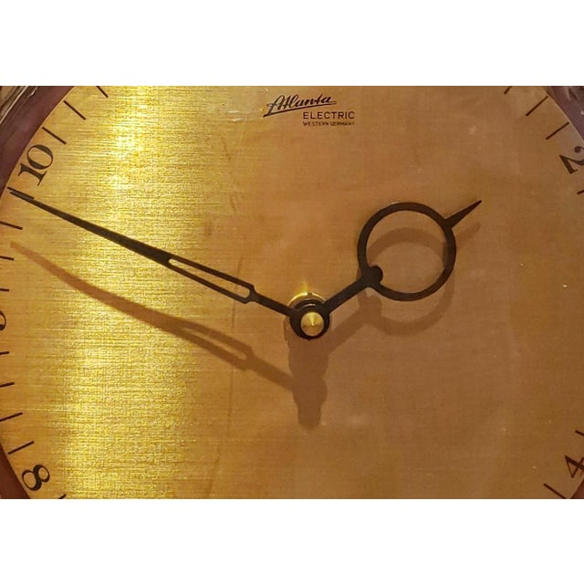 A '60s-era modernist wall clock in teak, brass, and black metal from Atlanta Electric of West Germany. Powered by a...