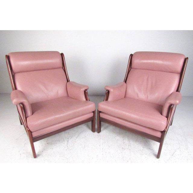 This stylish pair of Scandinavian Modern lounge chairs boast leather high back seats, sturdy sculptural teak frames and...
