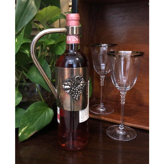 This is for a wonderful Vintage bottle caddy / handle / wine server. It slips over the top of the bottle and stays snug...