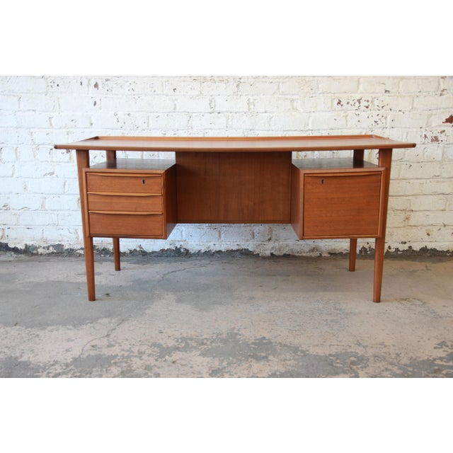 Offering an exceptional Danish Modern teak floating top desk designed by Peter Løvig Nielsen for Løvig Dansk. The desk...
