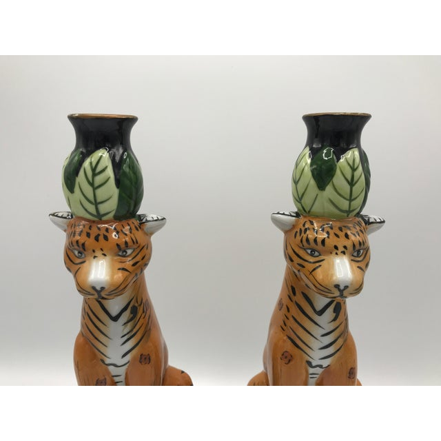 Offered is a fabulous, pair of 1980s painted porcelain candlestick holders. The pair has a beautiful, perched leopard...