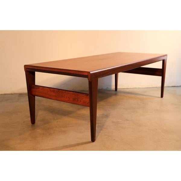 This coffee table is made of rosewood and features two extensions. One of the extension features a formica top. It was...
