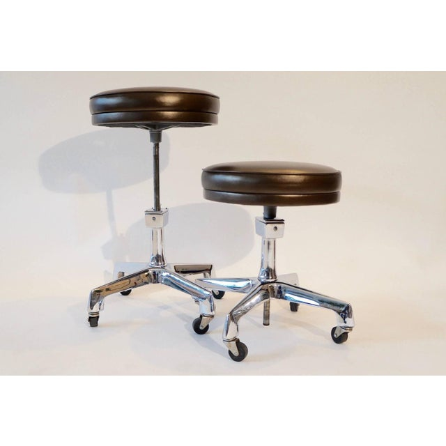 Two F.F. Koenigkramer adjustable Industrial stools. Re-upholstered in a metallic chocolate brown leather. Also sold...
