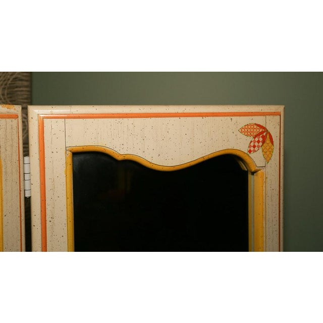 A charming mid-century vintage tri-fold mirrored screen is available for sale. The screen has a cream hand painted...