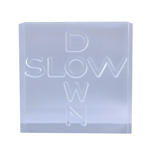 Offering a vintage Pop Art sculpture that has SLOW DOWN engraved in a Lucite block, circa 1960s. This chunky sculpture is...