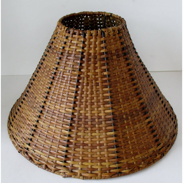 Vintage single uno lamp shade created from woven wicker and black metal binding. The fiber has a protective clear lacquer...