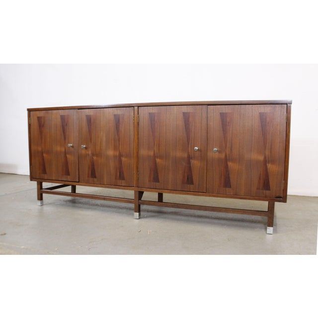 Offered is a vintage mid-century modern walnut credenza with four parqueted doors and brushed aluminum caps on the front...