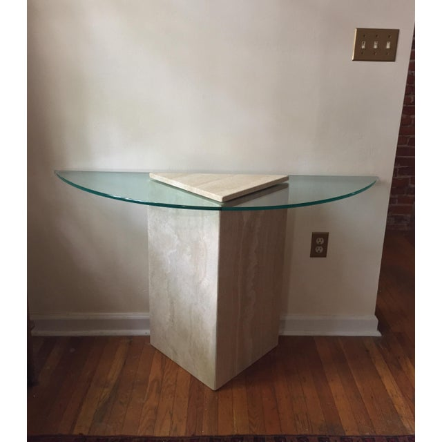 """A hollow triangular travertine pedestal topped by a demilune-shaped sheet of glass. A 0.5"""" inch thick triangular sheet of..."""