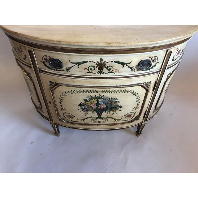 Beautifully painted demilune cabinet. The base paint is an ivory/creamy tone with antiquing. Gold painted accents...