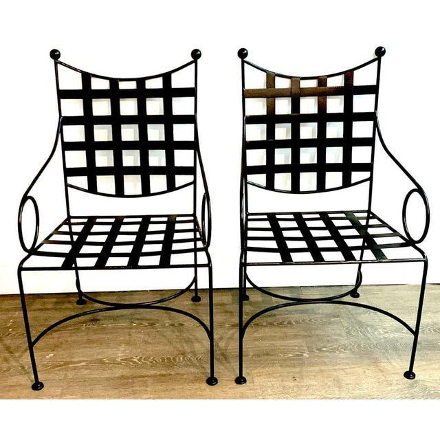 "Pair of Salterini style woven wrought iron patio armchairs, 2nd pair available Measures: 25"" arm height 17"" seat height."