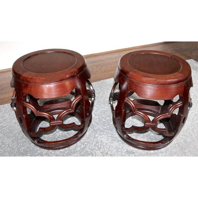 Pair of Chinese nicely carved hardwood garden stools. Each with carved and pierced decoration to the four supports and bases.