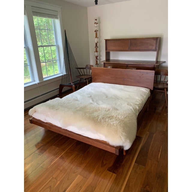 Platform bed studio crafted in the style of George Nakashima circa 1960s. It features a mounted walnut slab headboard that...