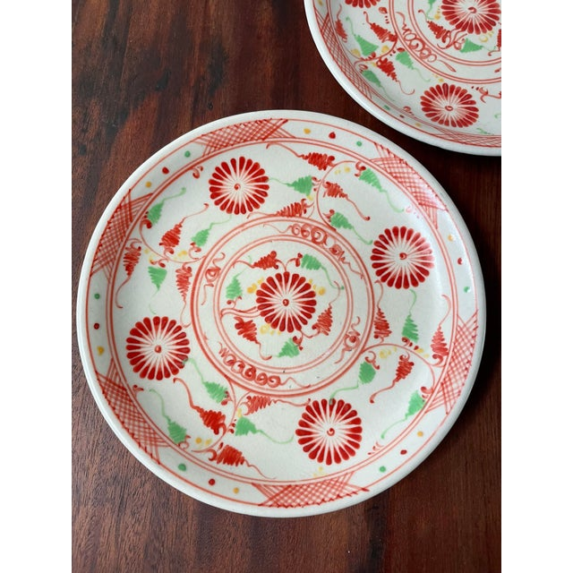 Vintage 20th century hand-painted botanical serving plates, featuring flat red flowers and red-and-green vines. The rim of...