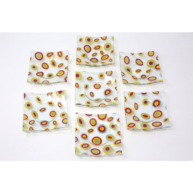 A set of seven small pressed glass dishes, with a square form and abstract/atomic red, yellow and gray pattern. Use as...