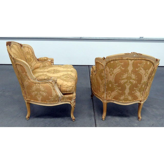 Pair of Drexel Heritage for Caldwell distressed painted bergeres with gilt accents and textured upholstery.