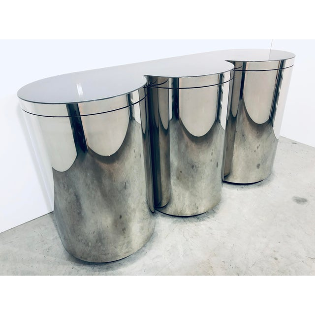 Mirror polished stainless steel credenza with three rotating cylinders and smoked plexiglass surface. The interior of the...