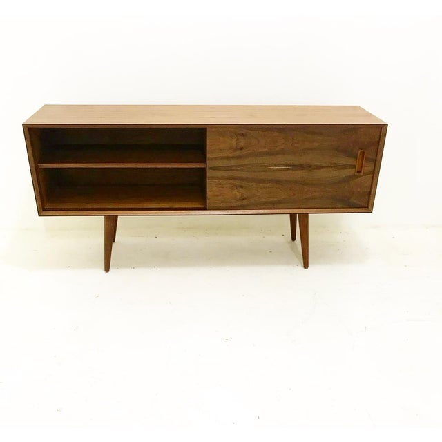 Sleek mid century modern style Walnut credenza. Hand crafted out of domestic Walnut plywood. Includes 2 sliding doors,...