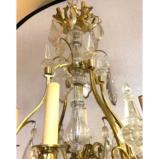 Beautiful French bronze and rock crystal chandelier in the style of French designer Maison Bagues. It has 4 lights,...