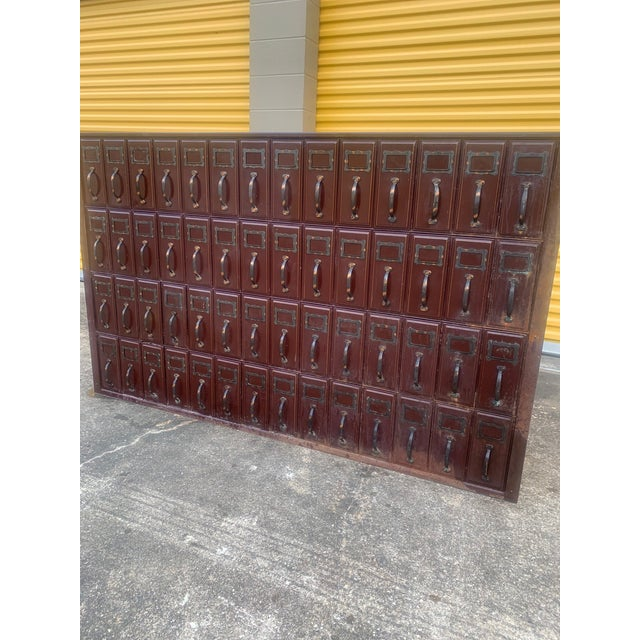 A Large Vintage Red metal courthouse ledger file cabinet with 56 drawers arranged horizontally in 4 rows of 14. With a...