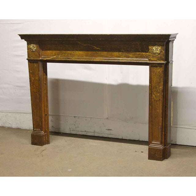 Simple Regency style faux marble wooden mantel with two brass florets. There is general wear from age and use-see photos....