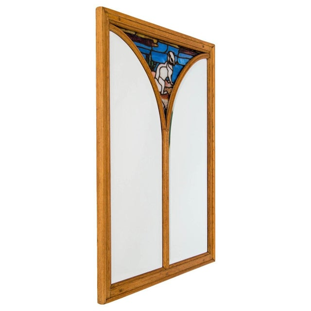Large light oak French mirror with leaded and reverse painted stained glass upper section portraying an ermine, circa...