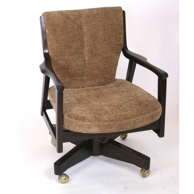 A swivel, adjusting desk chair in walnut with new upholstery. Shaped arms with tapered, channeled back.