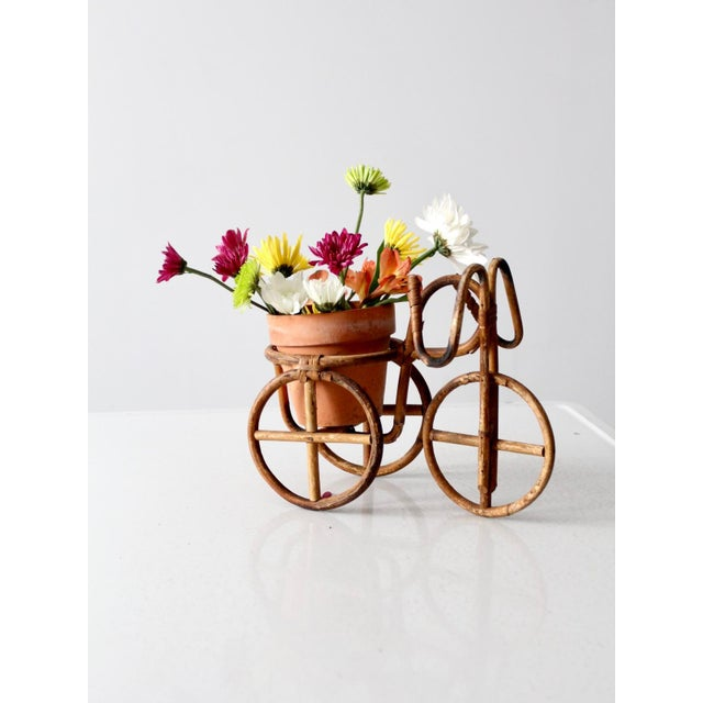 A charming bentwood rattan planter holder. The bicycle shaped pot or vase holder features a raised round platform holder...