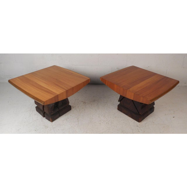 This wonderful pair of vintage modern end tables by Witco feature carved dark wood bases with a sculpted blonde wood top....