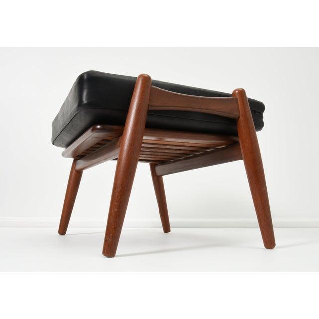 Hans Wegner ottoman with black leather cushion Denmark, 1950s GETAMA Teak, leather Measures: 23.5 H x 19 D x 15 H. Signed...
