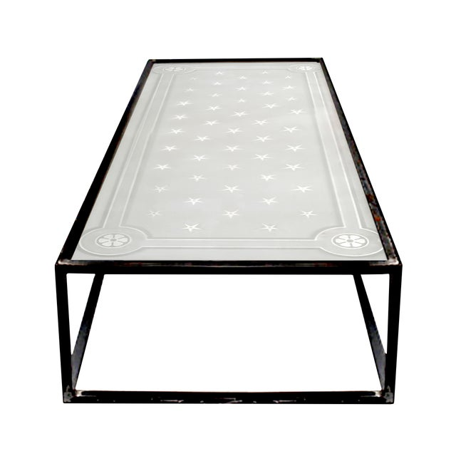 Large French etched glass coffee table with steel base. The glass rests on top of the steel base with a steel frame that...