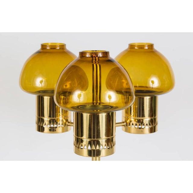 1960s Hans-Agne Jakobsson candelabrum for Markaryd. Amber glass and brass triple votive candelabrum. Elegant and refined...