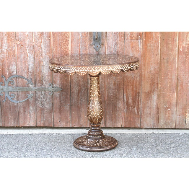 Anglo-Indian rosewood round side table that stands on a pedestal base all inlaid by hand. Topped with a smooth top that's...