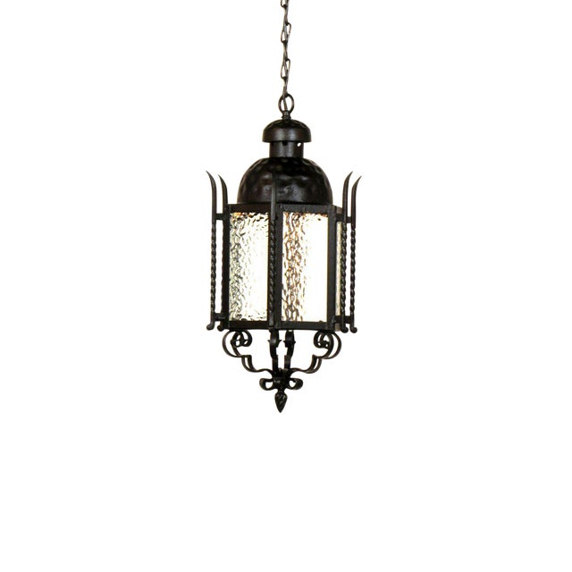 Pair of wrought iron lanterns with hammered glass panels. Can be used as exterior or interior lanterns. Textured glass and...