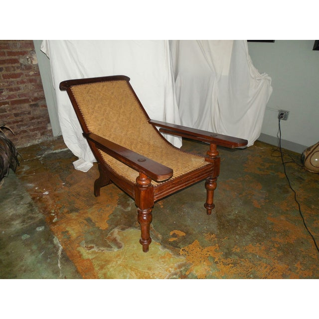 Exotic and authentic antique Anglo-Indian plantation chair with outstanding original caned seat and turned legs. The back...
