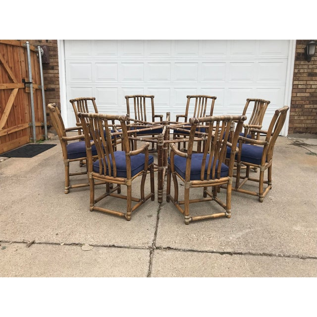 Monumental McGuire dining table with 8 bamboo arm chairs. Beautiful bamboo rods are bound together with McGuire's...