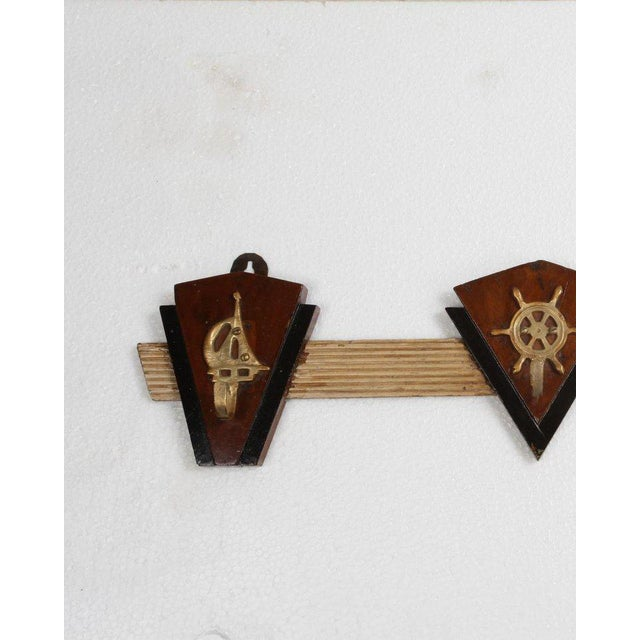 A group of teak, rosewood and brass coat hooks with nautical motifs. Reeded and painted bar with brass nautical hooks...