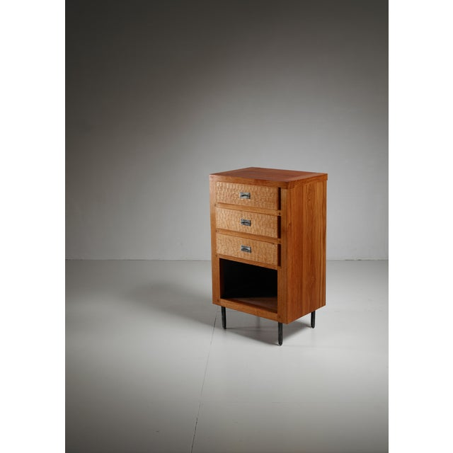 A Jean Touret oak cupboard for Atelier Marolles. The cupboard has three drawers with a carved front and iron pulls. This...