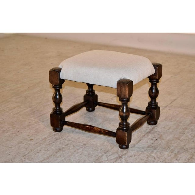Late 19th century turned oak stool from England with a newly upholstered top in linen. The legs are hand-turned and are...